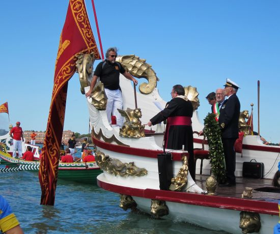 "Aboard the ""Serenissima,"" the priest is reading the blessing of the wreath, as the admiral awaits his cue."
