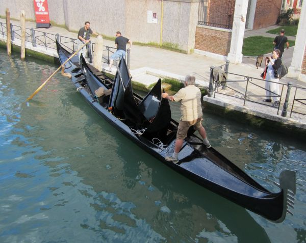 A better suggestion: Dragoon a real gondolier who's just walking by to row it the right way: All the weight over on the right side, making the boat tilt just enough to pass under with no problem. As long as nobody breathes.