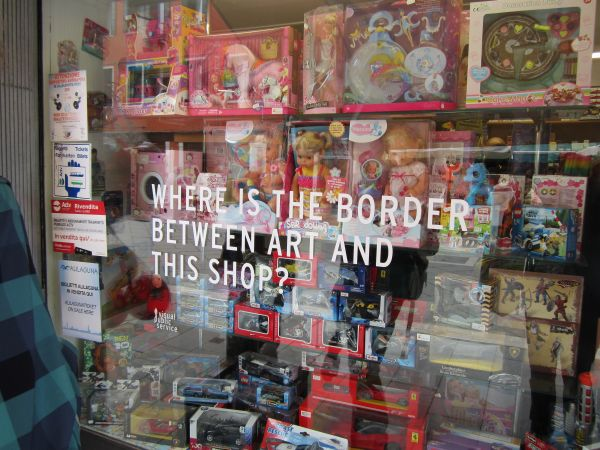 Interesting question. This shop sells toys, cigarettes, candy, and lottery tickets. Which leads me to conclude that there is no border between art and this shop, just like there's no border between Italy and Slovenia now that they're all part of the EU.