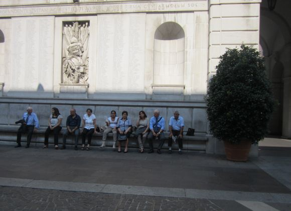 Matteo's family, plus Lino, sat against the wall of City Hall, facing the Palazzo, until the sun rose so high that the shadow disappeared.  Then we went inside to wait.