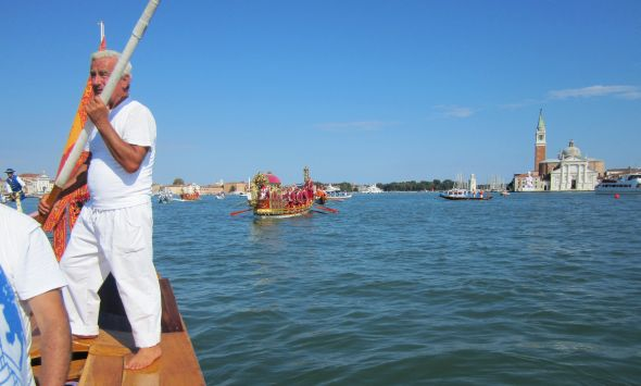 "The indefatigable Dino Righetto on the stern of our six-oar balotina.  The ""bissone,"" or fancy boats, are coming up behind us to start the procession."