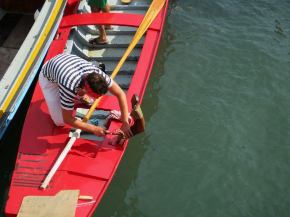 Gondolier Said Rusciano pounds the final blows onto his forcola before the regata of SS. Giovanni e Paolo.  Red is the color of the winner's pennant, but in this case, it wasn't the color of the winner's boat.