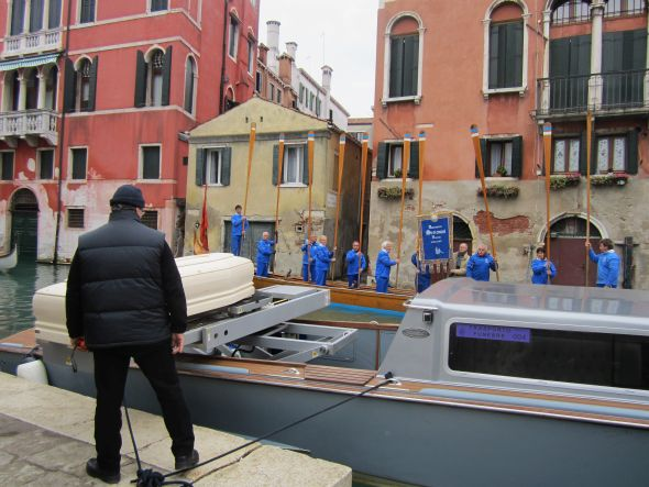 "As the casket is placed onto the fancy platform, the rowers from the Settemari club execute an ""alzaremi.""  In 1979 Da Preda was voted ""Venetian of the Year,"" an annual recognition bestowed by the club.  The commemorative plaque was placed on the casket during the service."
