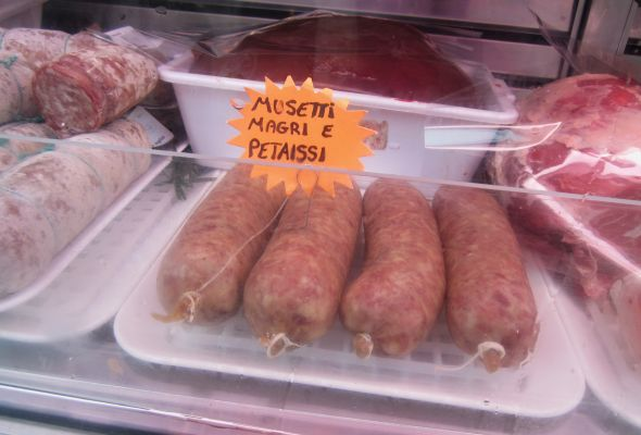 "These are some musettos (""musetti"") in the butchershop window.  Alberto has written that they are petaisso, intending it as an irresistible appeal.  Better musettos than people, I always say."