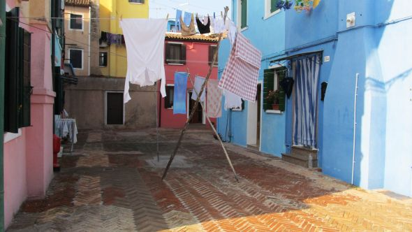 On the island of Burano, housewives can still rig up their temporary clotheslines the way women did in Venice a century ago.  You had to take turns for certain spaces in Campo Santa Margherita.  I like this method, it's simple, cheap, and efficient.  What else is there?