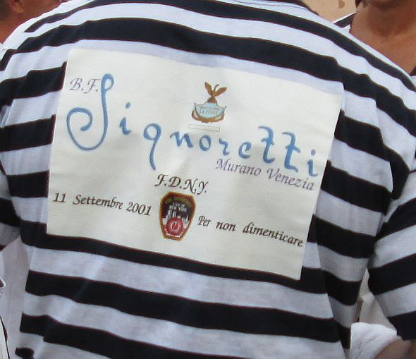 "Racers are now permitted to wear a sponsor's badge, and Signoretti's name was on several champions' backs -- here, Franco ""Strigheta"" Dei Rossi, at the regata of Redentore 2014.  Notice the addition of the link with the firemen of New York -- ""per non dimenticare"" -- to not forget."