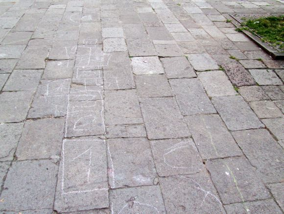 "The game is on, Watson -- here, the traces of hopscotch, known in Italy as ""campana""or ""mondo"" (""bell"" or ""world"").  Nice to know there's something other than soccer going on here."