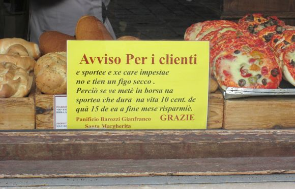 Even the baker in Campo Santa Margherita has to deal with economic complaints, in this case from his customers.  But they're not nagging about the cost of bread, but the fact that he's charging 10 cents per plastic bag if they want one to take the food home in.  Written in Venetian, it says: ""