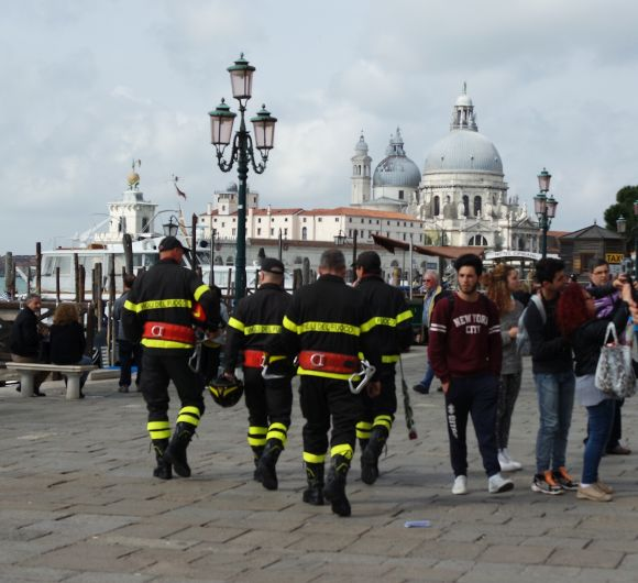 A quartet of firemen leaving the ceremony of the flag-raising in the Piazza -- one is already armed with his rose.