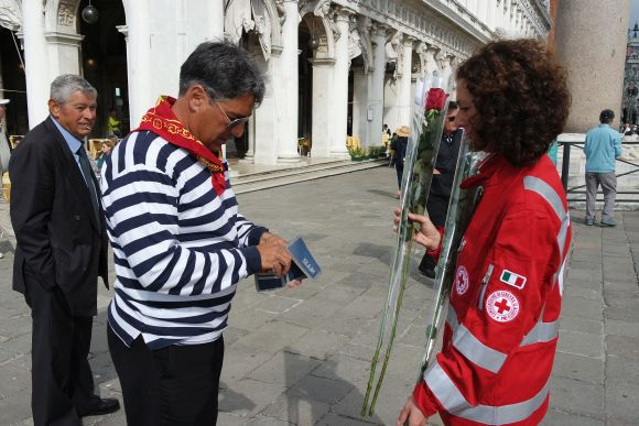 "And gentlemen must acquire a long-stemmed red rose (the ""bocolo,"" in Venetian) to bestow on their lady love(s).  Here, gondolier Marco Farnea buys two -- one for his wife, the other for his gondola.  It's an extra-festive occasion, too, considering it's his name-day."