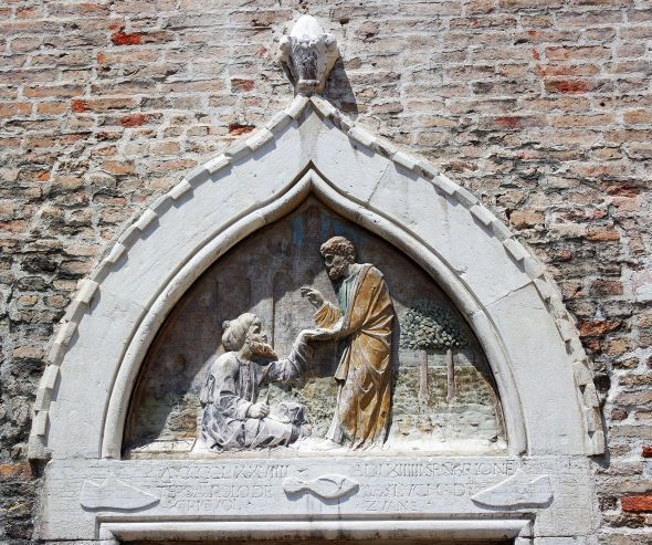 This relief sculpture over the main door of the Scoletta dei Calegheri in Campo San Toma' shows the miracle of San Marco healing the injry suffered by Aniano while repairing his sandals. Saint Aniano became the patron saint of the guild.