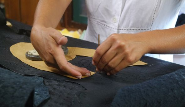 Tracing the shoe's pattern onto a sheet of ostrich-skin is careful work, what with the bumps and all.