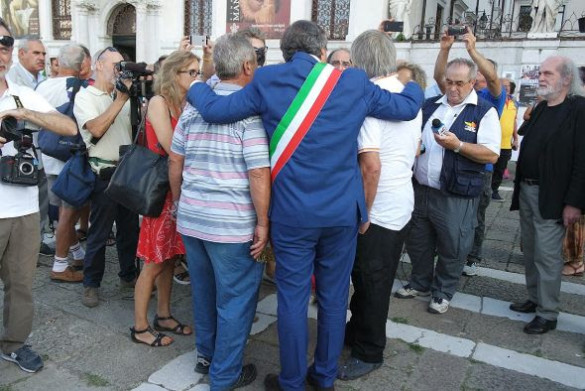 "The ceremony gets underway with photo-worthy hugs by the mayor, Luigi Brugnaro, wearing his official sash. to their right, the white-haired man in the black jacket is Mario Eremita, the artist who designed and painted the ""palio,"" or banner, depicting the Regata Storica. This is new this year and is loaded with symbolism."