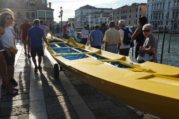 So let's get these boats in the water and out of here. In no particular order, the yellow boat is rolled on a small trolley to the edge of the steps to the canal, where some pieces of red carpet have been placed to ease the slide.
