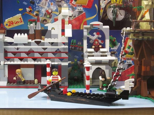 "A gondola and its -lier made of Lego pieces. I wonder if it floats? Or sings? Or shouts ""Oy!"" when it gets to the corner of the table?"